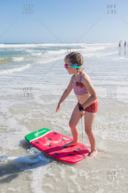 Girl watching the waves while standing on her body board at the beach