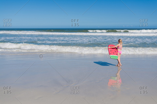 Girl carrying a body board while walking on a sandy beach