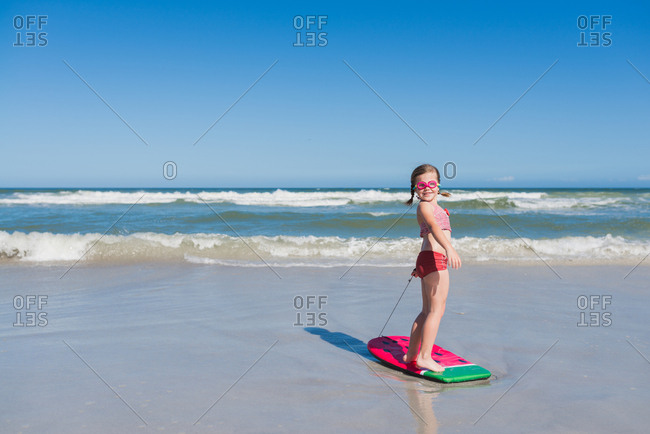Smiling girl standing on a body board at the beach