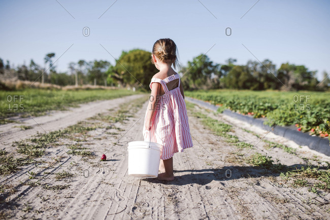 Toddler standing barefoot on dirt road