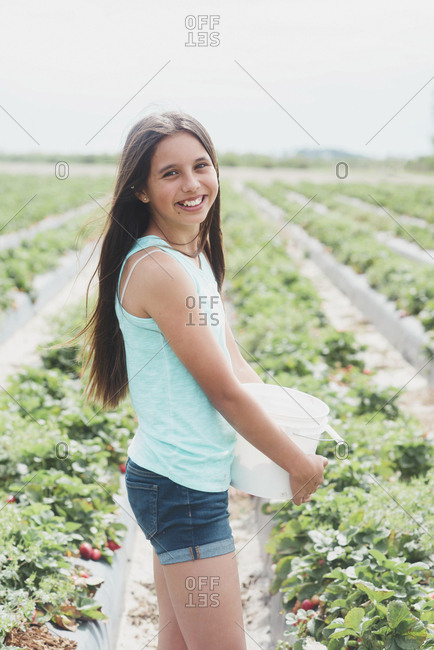 Teen girl in strawberry field