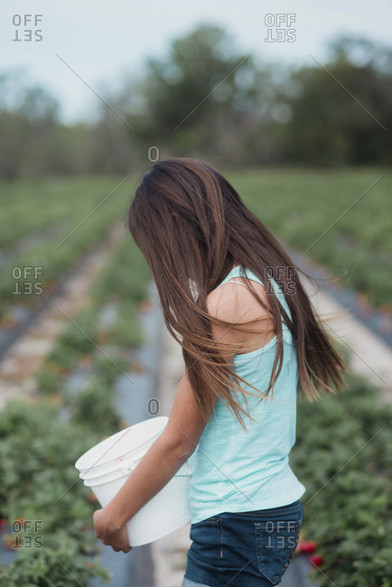 Teen girl holding a bucket in a strawberry field