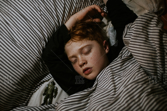 Young boy deep asleep snuggled in bedclothes