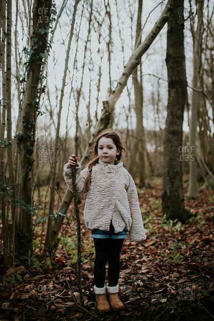 Full length portrait of little girl in woods holding staff
