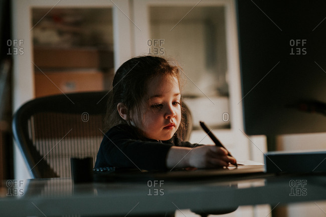 Little girl sitting in home office using stylus on graphics tablet