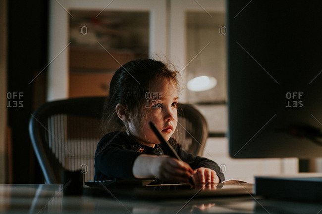Little girl looking at computer monitor while using stylus on graphics tablet