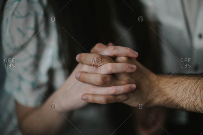 Detail shot of hands of a man and a woman with interlaced fingers