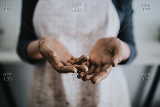 Potter holds out hands covered in clay