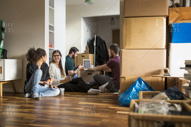 Group of friends resting on floor surrounded by moving boxes