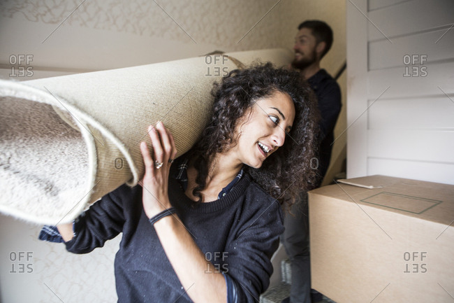 Woman and man carrying carpet while moving house