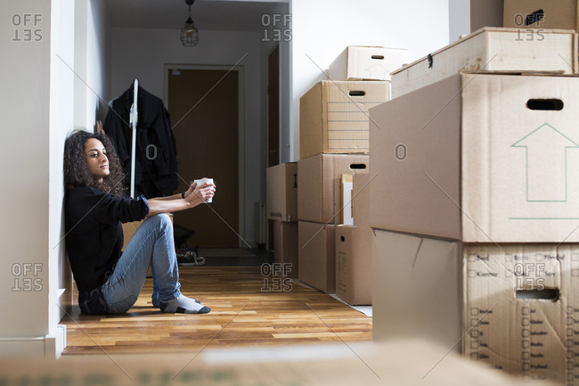 Woman resting on floor while moving house