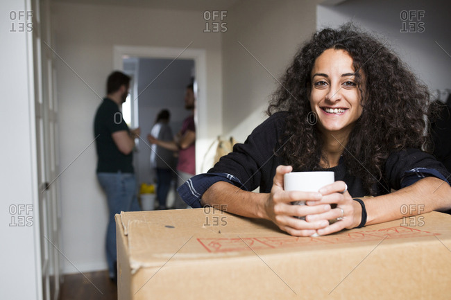Happy woman leaning on box, group of friends in background