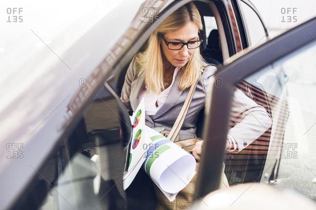 Woman with blueprints getting out of car
