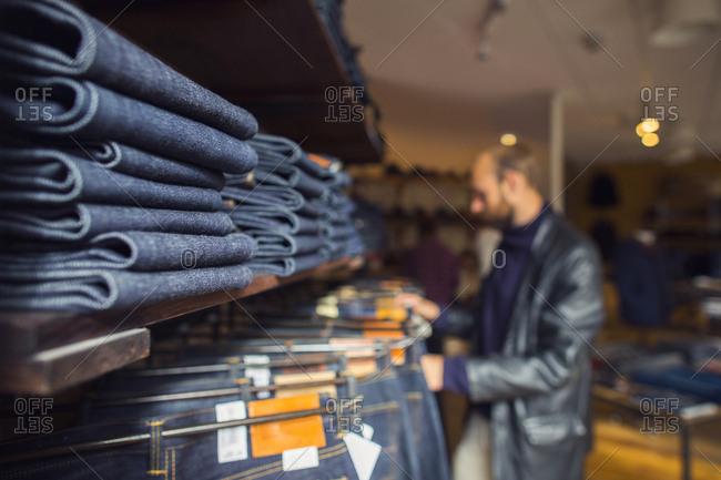 Man choosing jeans in store
