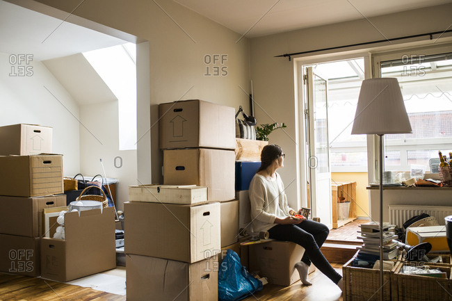 Woman sitting on box while moving house