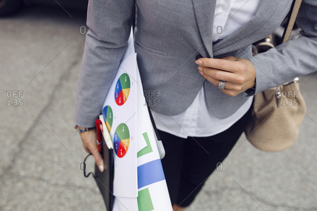 Mid section of woman carrying printouts