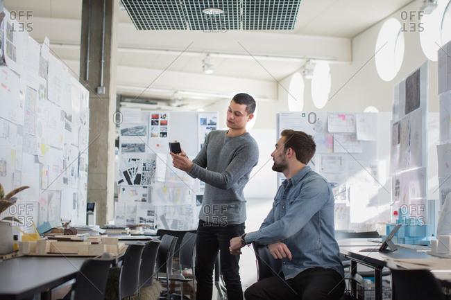 Designers looking at smartphone in creative workspace