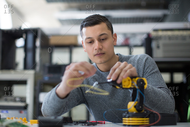 Young adult working on robotic arm
