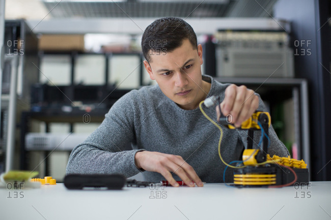 Young adult studying robotic arm