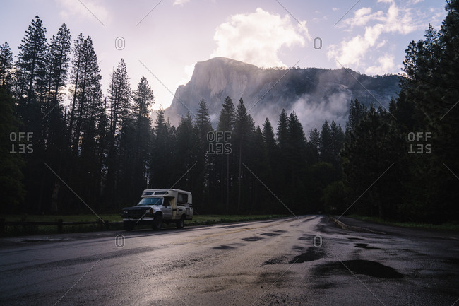 Vehicle on road by trees against mountain at Yosemite National Park
