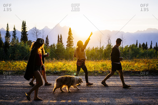 Friends with dog walking on road at dusk in Grand Teton National Park