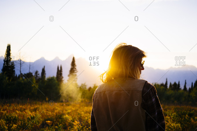 Rear view of hiker standing on field against sky at Grand Teton National Park