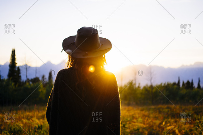 Rear view of female hiker in hat standing on field against sky at National Park