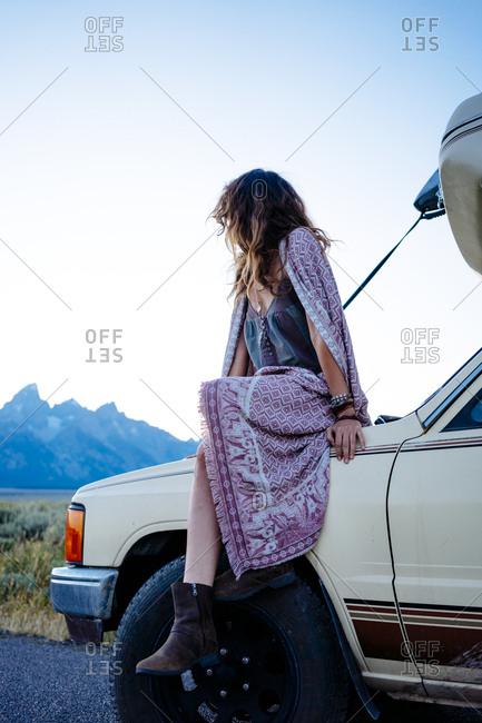 Woman in blanket sitting on caravan enjoying the view at park