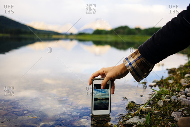 Cropped image of woman photographing lake against sky through smart phone