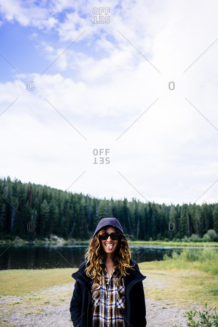 Happy woman in hood standing in front of lake