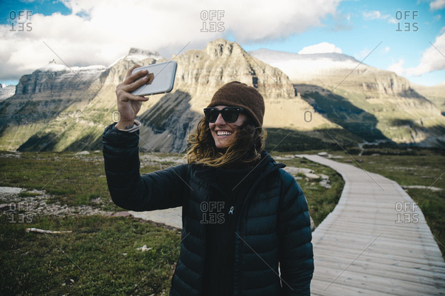 Smiling woman taking selfie against mountains at Glacier National Park