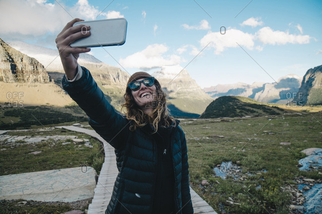 Happy woman taking selfie through mobile phone while standing on boardwalk at Glacier National Park