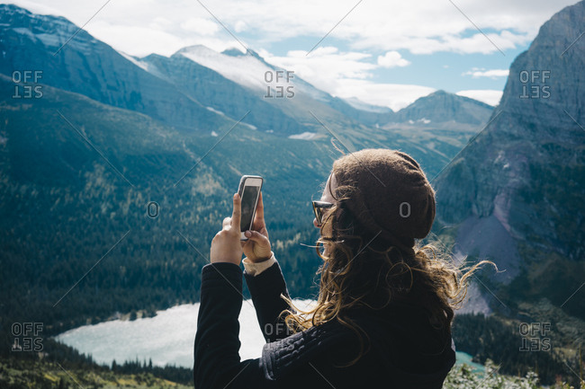 Side view of woman photographing through mobile phone while standing by mountains at Glacier National Park