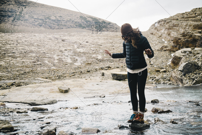 Full length of woman standing on rock amidst lake by mountain at Glacier National Park