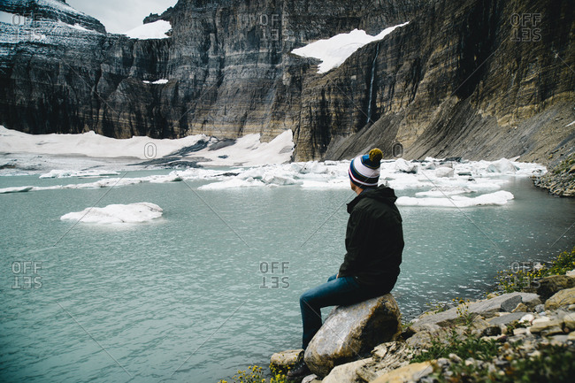 Young man sitting on rock by lake against snowcapped mountain at Glacier National Park