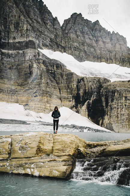 Woman standing on rock d by lake against mountain at Glacier National Park