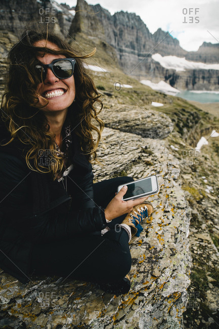 Happy mid adult woman using phone while sitting on rock formation at Glacier National Park