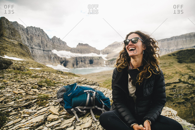 Happy woman with backpack sitting on rock at Glacier National Park