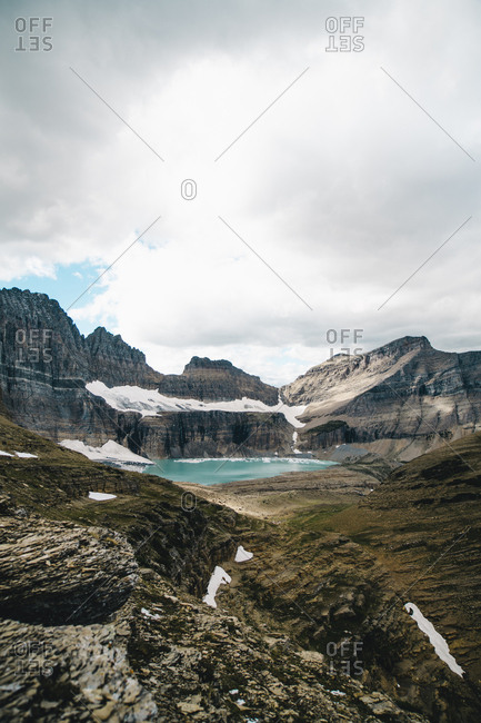 Idyllic view of lake and mountain range against cloudy sky at Glacier National Park