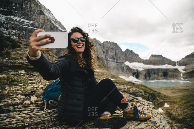 Happy woman taking selfie through mobile phone while sitting on rock at Glacier National Park