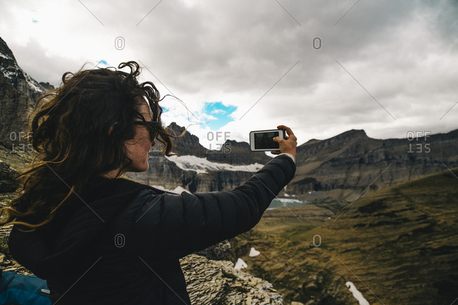 Woman taking selfie through mobile phone while standing on mountain against cloudy sky at Glacier National Park