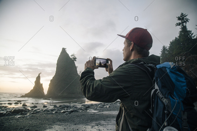 Young hiker photographing ocean through mobile phone at Olympic National Park