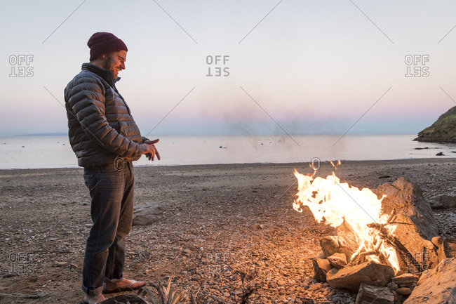 Smiling man looking at campfire while standing on sandy beach during sunset