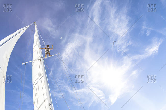 Low angle view of man standing on sailboat mast against blue sky during sunny day