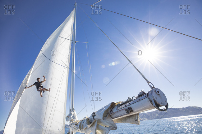 Man climbing the mast of a sailboat on a sunny day