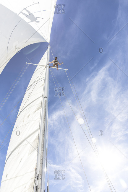 Low angle view of young man standing on crows nest of sailboat