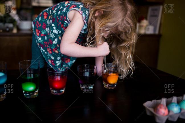 Little girl dying Easter eggs in glasses