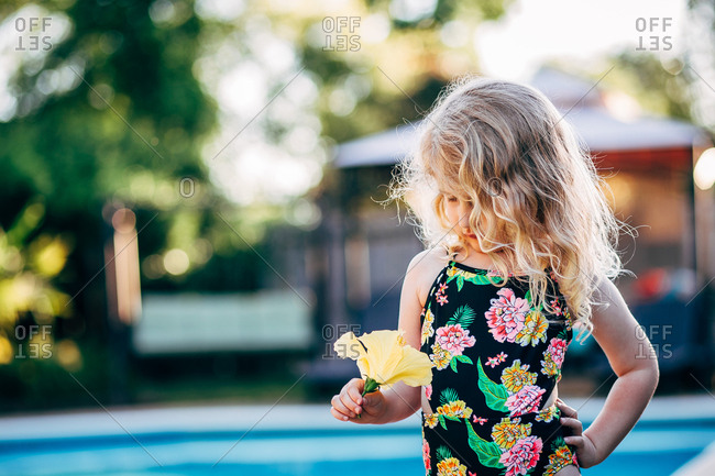 Little blonde girl holding yellow flower beside pool