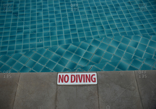 No diving sign on edge of swimming pool