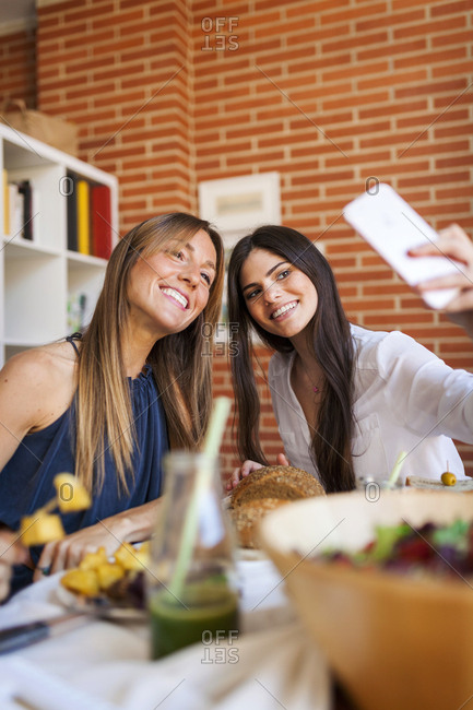 Two friends taking selfies while eating lunch together